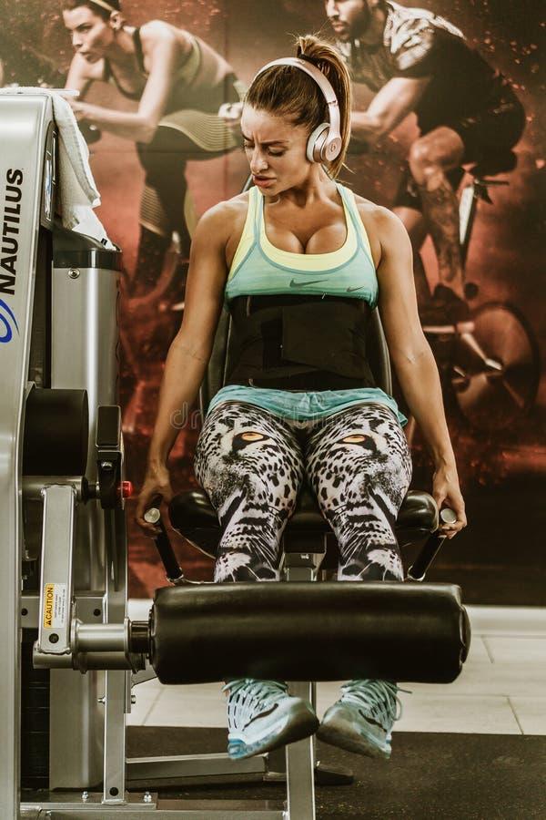 Frau, die mit Gewichten an der Turnhalle losstürzt stockfotografie