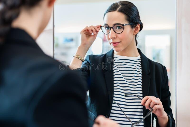 Frau, die mit Gläsern im Spiegel Optiker betrachtet stockfotografie