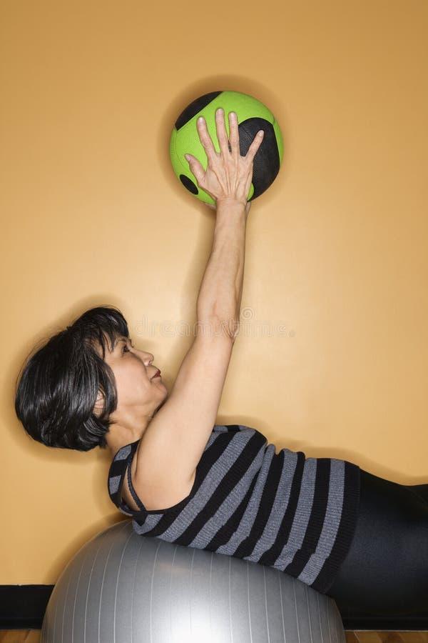 Frau, die mit Gymnastik-Kugeln trainiert stockbild