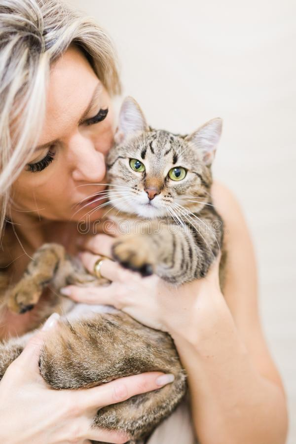 Frau, die mit Hauptkatze - reizendes Haustier spielt lizenzfreie stockbilder