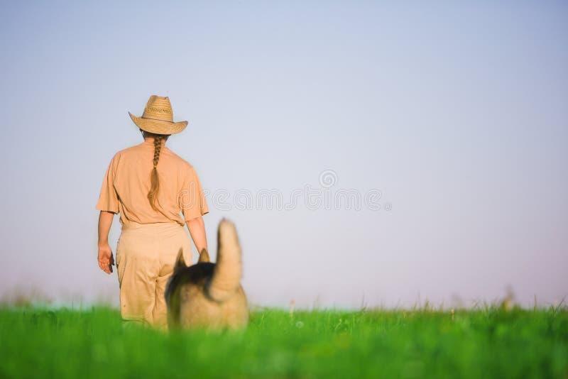 Frau, die mit Hund geht lizenzfreies stockbild