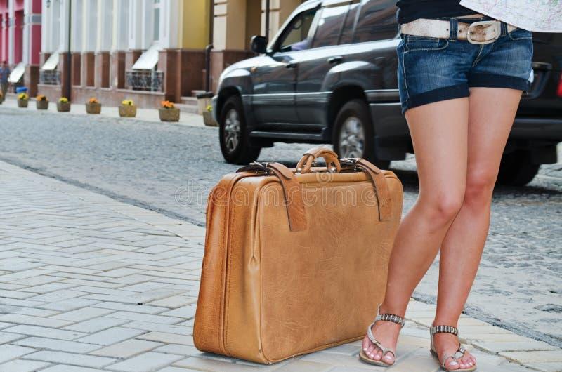 Frau, die mit ihrem Koffer in der Straße wartet lizenzfreie stockbilder