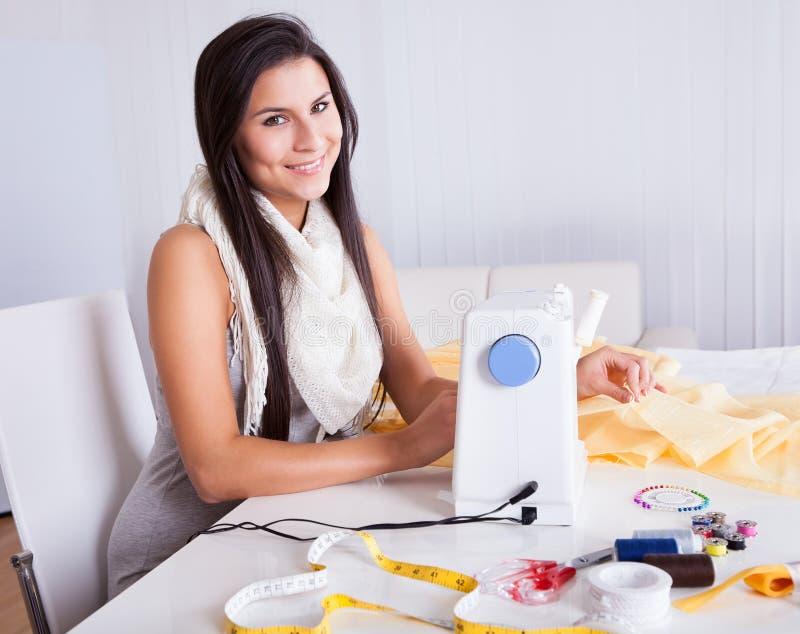 Frau, die mit ihrer Nähmaschine arbeitet lizenzfreie stockfotos
