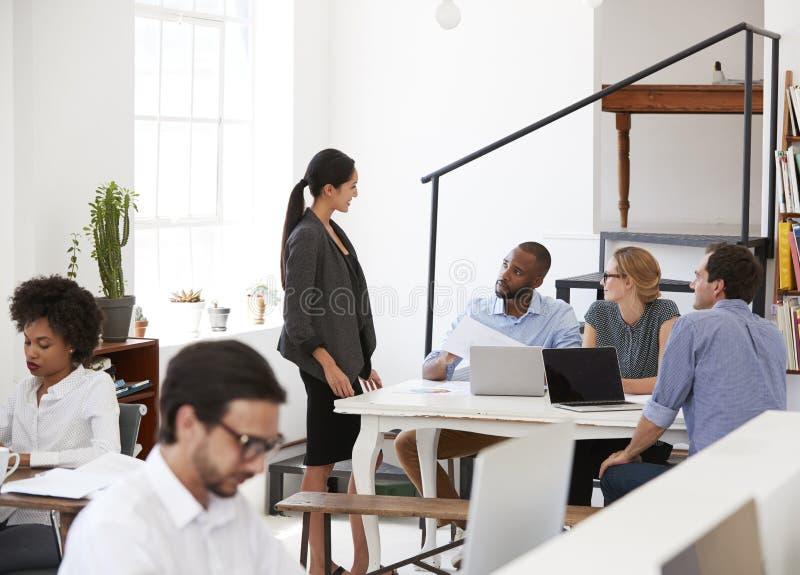Frau, die mit Kollegen an einem Schreibtisch im Bürogroßraum spricht lizenzfreies stockbild