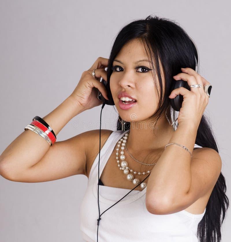 Frau, die mit Kopfhörern singt stockfoto