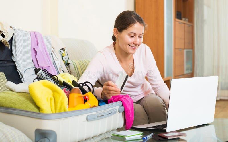 Frau, die mit Kreditkarte nahe Laptop und Gepäck sitzt stockbilder