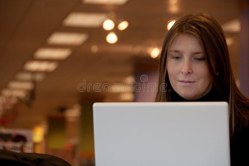 Frau, die mit Laptop arbeitet stockfotografie