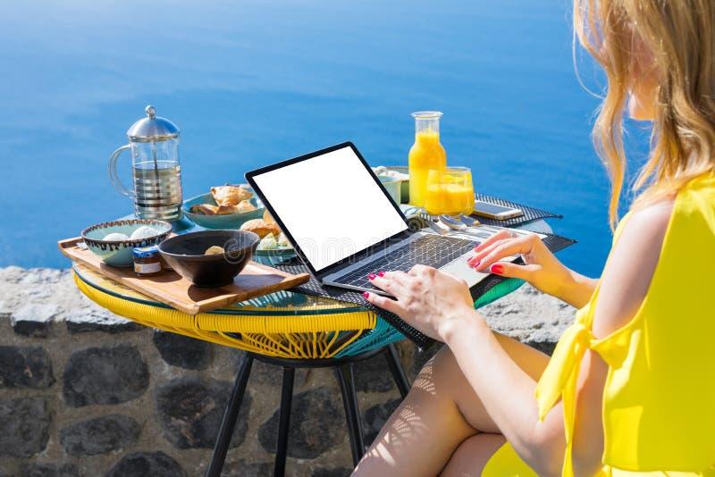 Frau, die mit Laptop-Computer beim Frühstücken auf Terrasse arbeitet lizenzfreie stockfotos