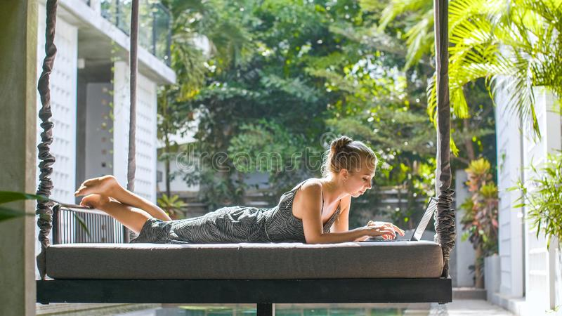 Frau, die mit Laptop kühlt stockbilder