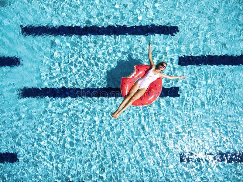 Frau, die mit lilo im Pool sich entspannt lizenzfreie stockfotografie