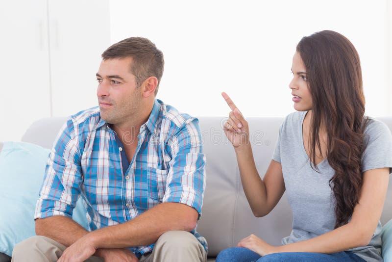 Frau, die mit Mann beim Sitzen auf Sofa argumentiert stockfoto