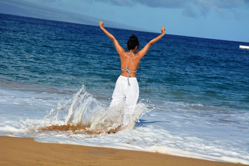 Frau, die mit Meereswogen spielt stockfoto