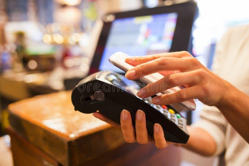 Frau, die mit NFC-Technologie am Handy, Restaurant, Ca zahlt lizenzfreie stockbilder
