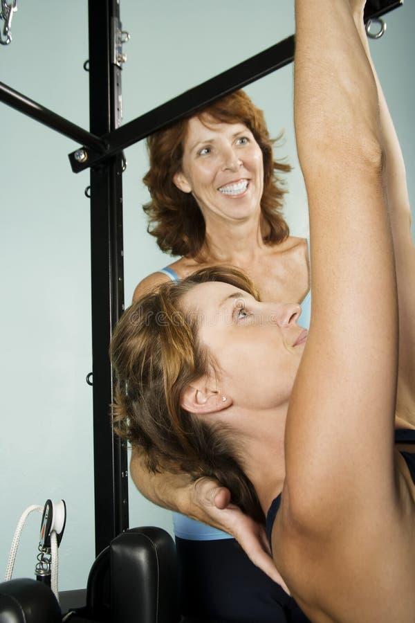 Frau, die mit persönlichem Kursleiter ausarbeitet stockbilder