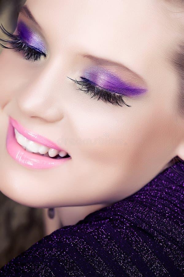 Frau, die mit purpurroter Augenschminke lächelt stockbild
