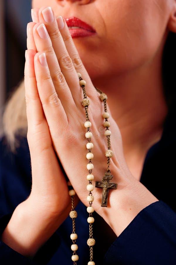 Frau, die mit Rosenbeet zum Gott betet stockfotos