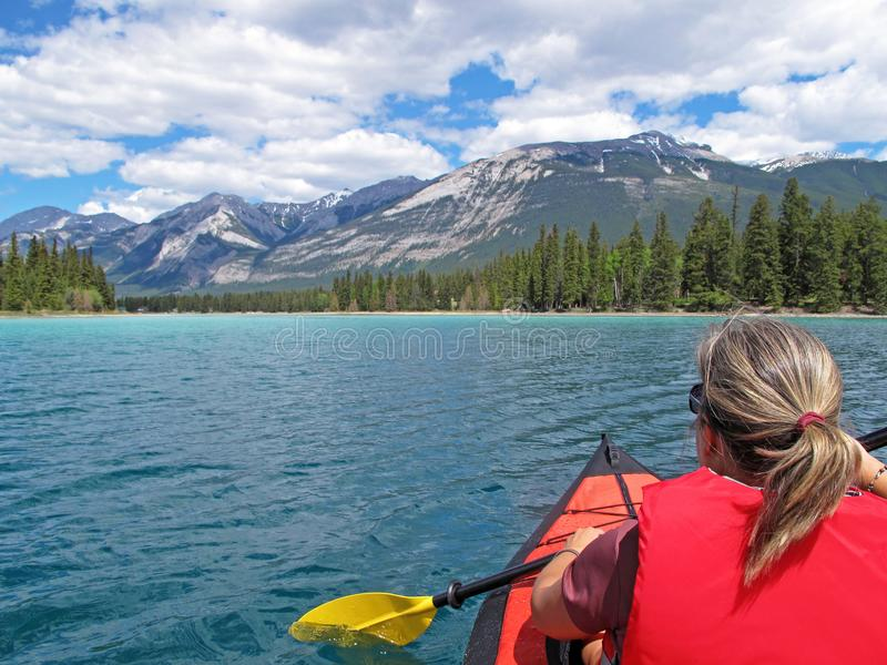 Frau, die mit rotem aufblasbarem Kajak auf Edith Lake, Jaspis, Rocky Mountains, Kanada Kayak fährt stockbild