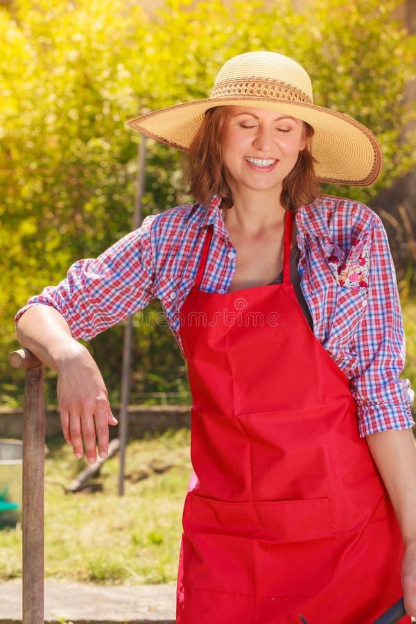 Frau, die mit Schaufel im Garten steht stockbild