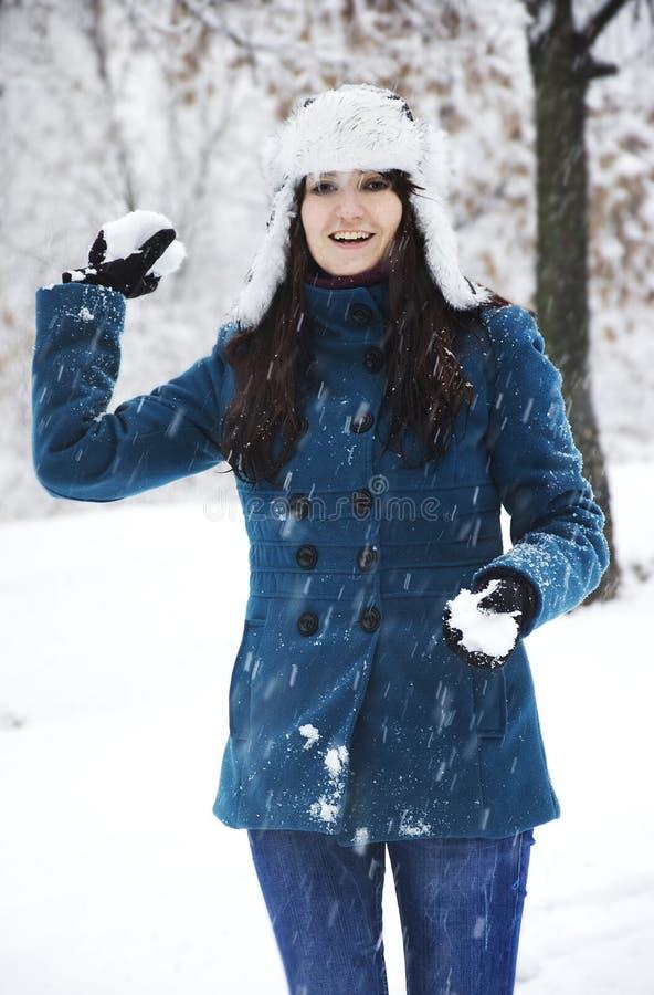 Frau, die mit Schnee spielt lizenzfreies stockfoto