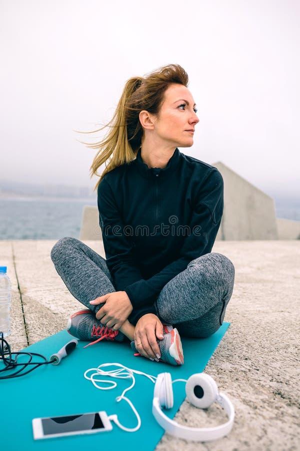 Frau, die mit Sportzubehör sitzt lizenzfreies stockbild