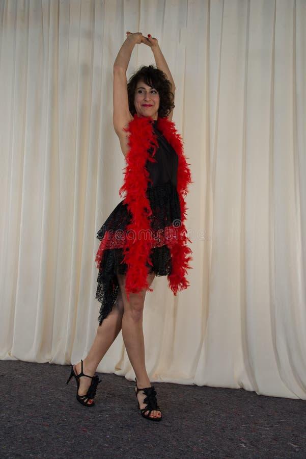 Frau, die mit Tanzenkostüm, mit roter Federboa aufwirft stockbild