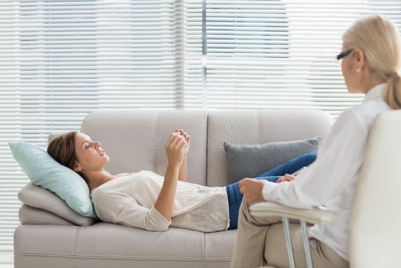 Frau, die mit Therapeuten beim Lügen auf Sofa spricht stockfotografie
