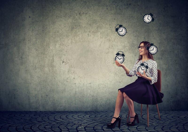 Frau, die mit Weckern jongliert lizenzfreie stockbilder
