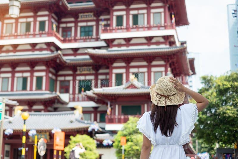 Frau, die mit weißem Kleid und Hut, asiatischer Reisender schaut zum Buddha-Zahn-Relikt-Tempel in Chinatown von Singapur reist gr stockfoto