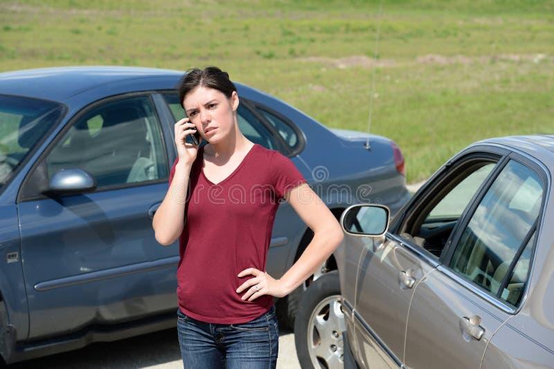 Frau, die Mobiltelefon nach Unfall verwendet stockbilder