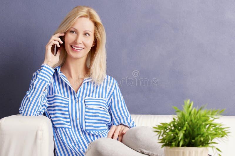 Frau, die Mobiltelefon verwendet stockfotografie