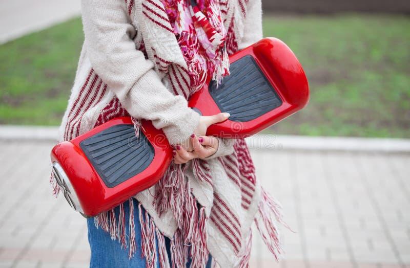 Frau, die modernen roten elektrischen mini segway oder Schwebeflugbrettroller hält lizenzfreies stockbild