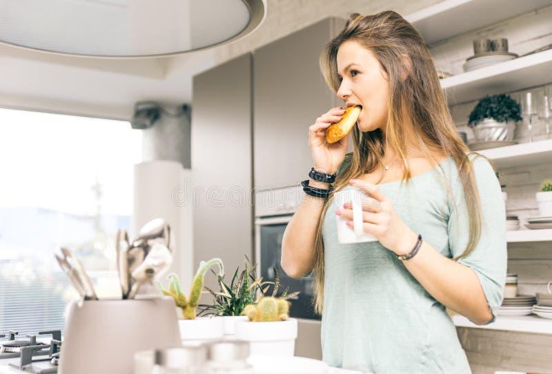 Frau, die morgens Hörnchen zum Frühstück isst stockbilder
