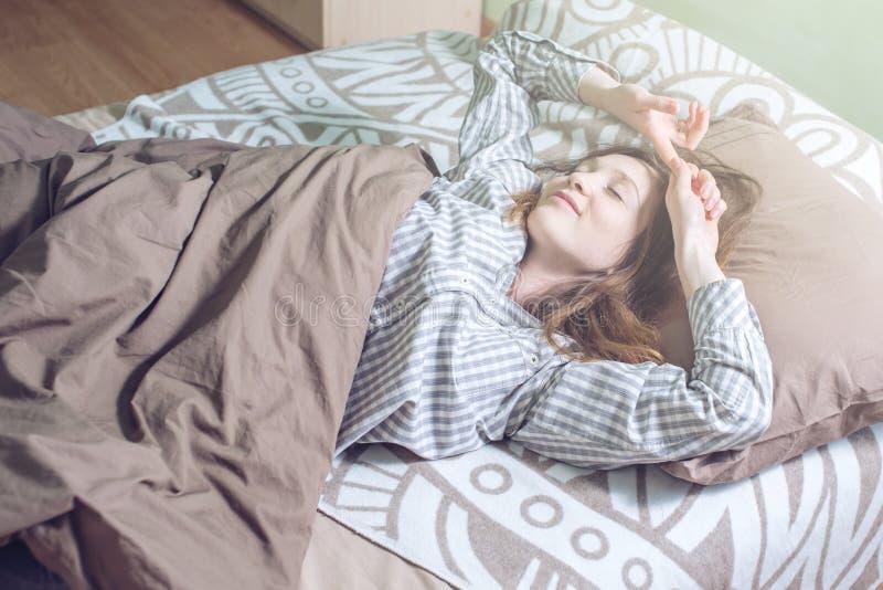 Frau, die morgens, Lügen schläfrig im Bett aufwacht lizenzfreies stockbild