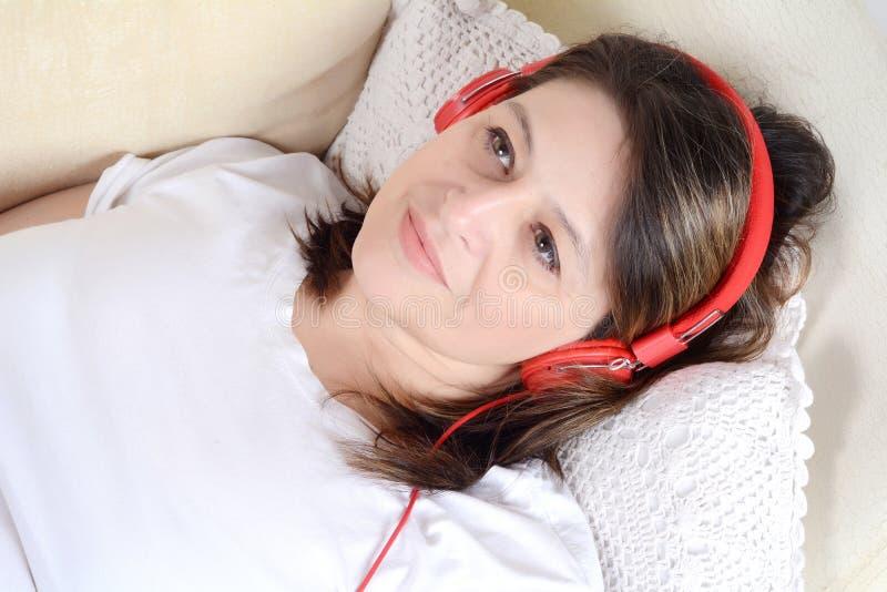 Frau, die Musik auf dem Sofa hört lizenzfreie stockfotografie
