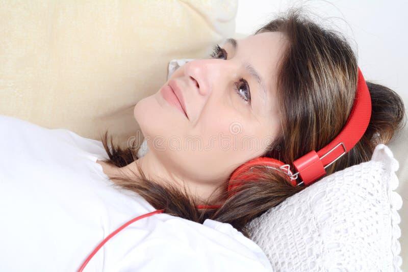 Frau, die Musik auf dem Sofa hört stockbilder