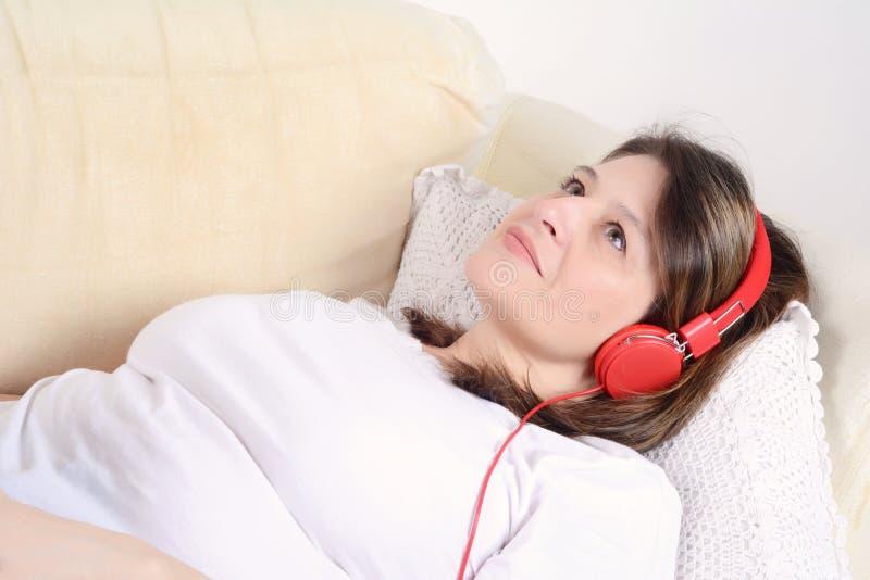 Frau, die Musik auf dem Sofa hört stockbild