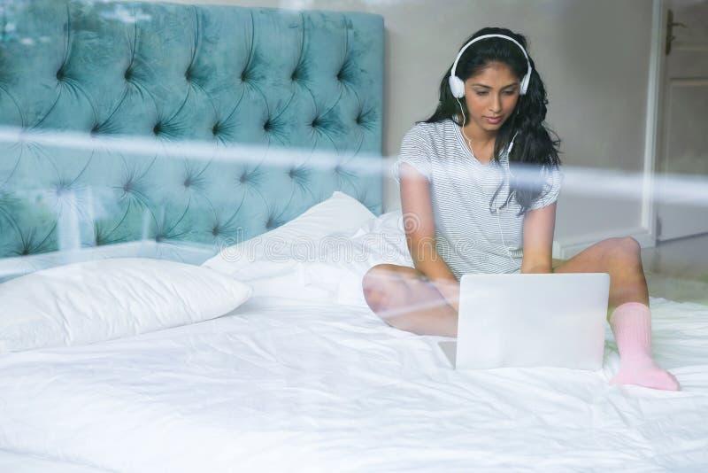 Frau, die Musik bei der Anwendung des Laptops hört lizenzfreie stockfotografie