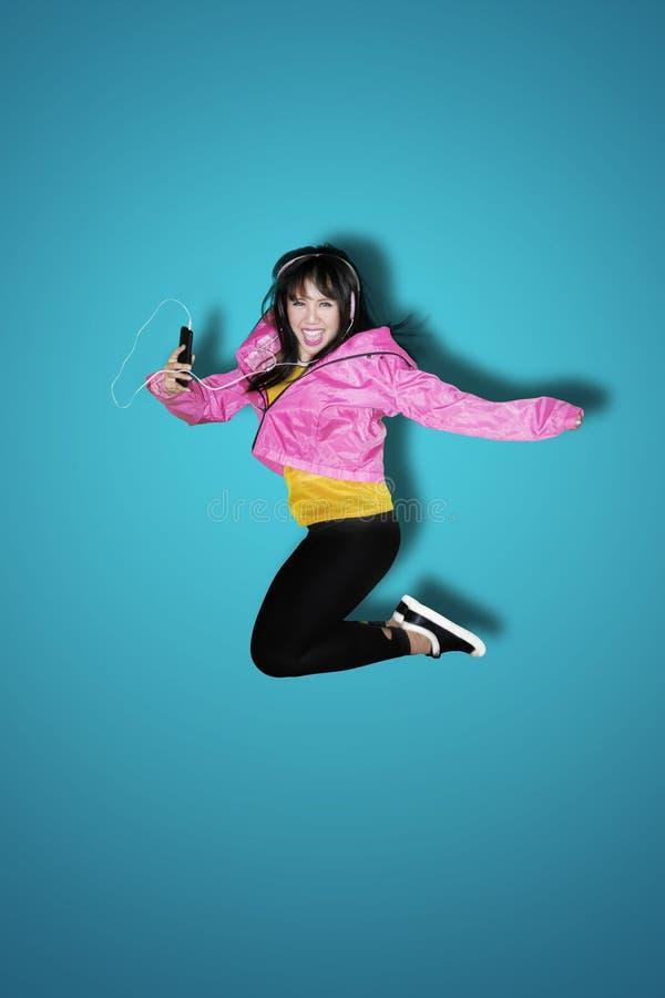 Frau, die Musik beim Springen hört lizenzfreies stockbild