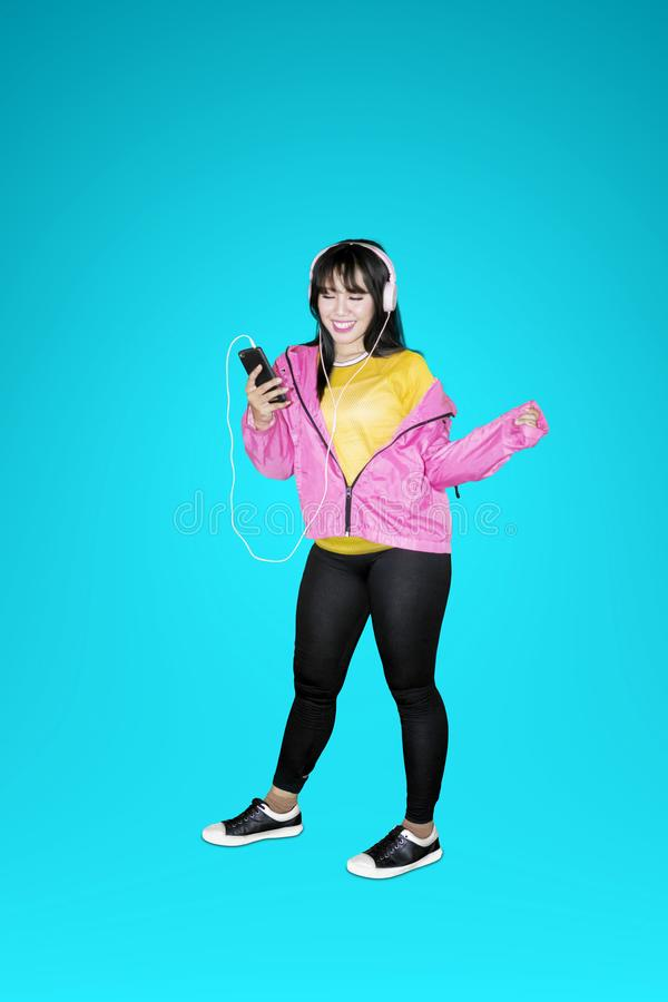 Frau, die Musik an einem Handy hört lizenzfreie stockfotos