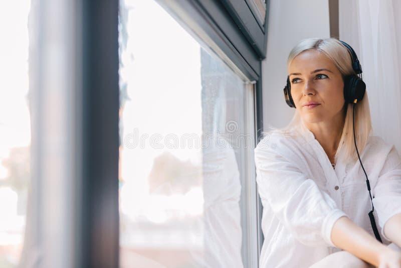 Frau, die Musik, heraus anstarrend das Fenster hört stockfotografie