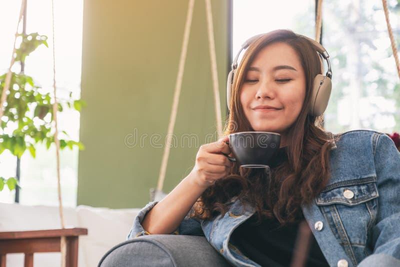 Frau, die Musik mit Kopfhörer beim Trinken des Kaffees mit dem Gefühl glücklich und entspannt im Café hört lizenzfreie stockbilder