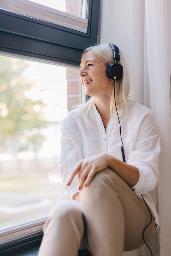 Frau, die Musik, schauend durch das Fenster hört stockbild