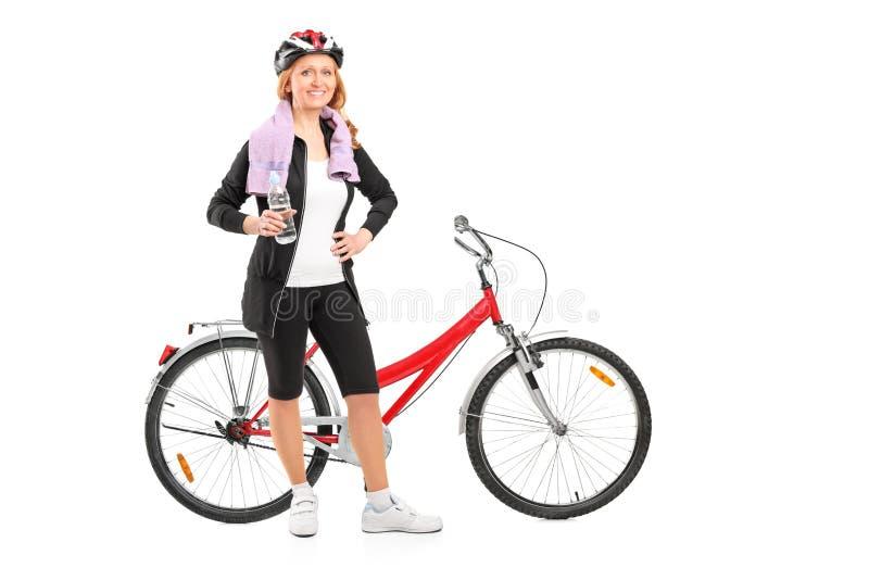 Frau, die nach dem Reiten eines Fahrrades stillsteht stockfotos