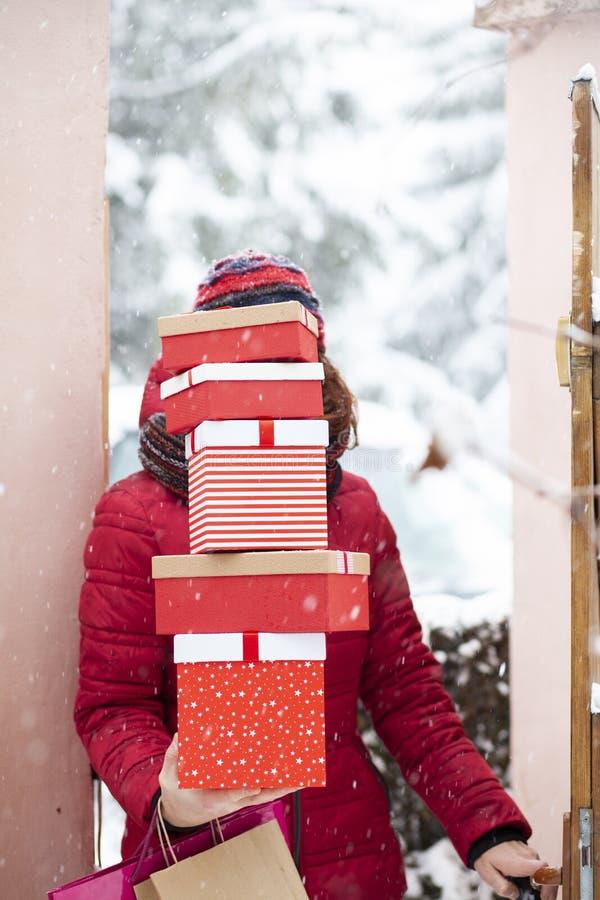 Frau, die nach Hause von Einkaufshaltenem Stapel von Weihnachtspräsentkartons zurückkommt lizenzfreies stockfoto
