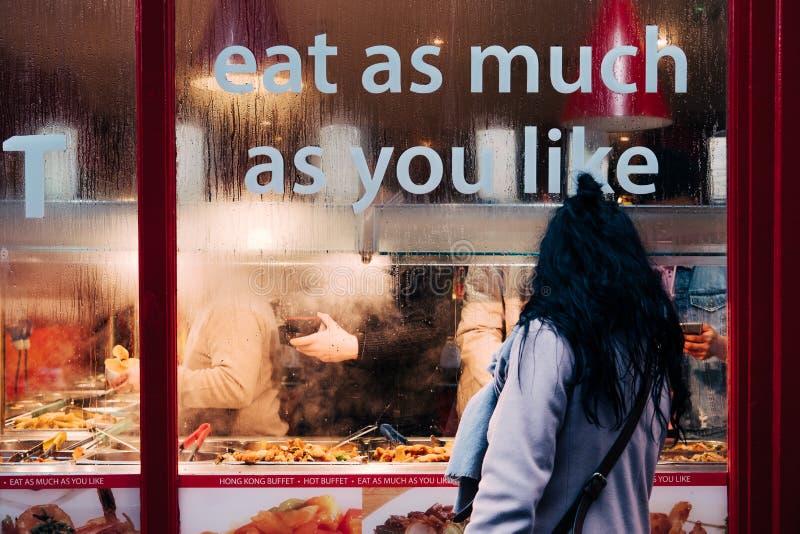Frau, die nach innen durch das Glas des chinesischen heißen Buffets in Chinatown, London, Großbritannien schaut stockbilder