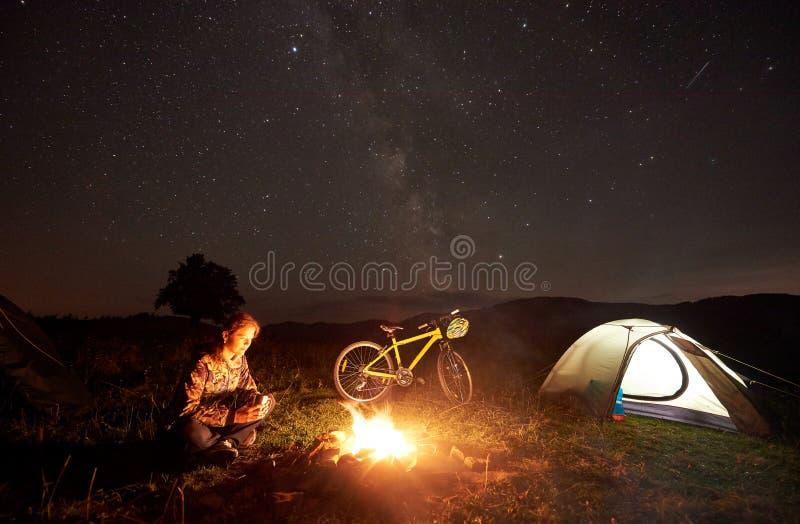 Frau, die nachts voll kampierend nahe Lagerfeuer, touristisches Zelt, Fahrrad unter Abendhimmel von Sternen stillsteht stockfoto