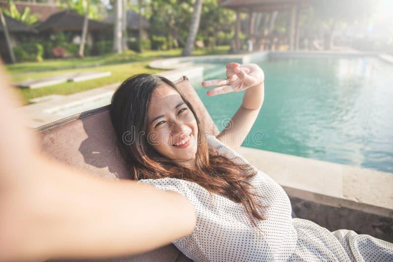 Frau, die nahe bei dem Pool sich entspannt und selfie nimmt lizenzfreie stockfotografie