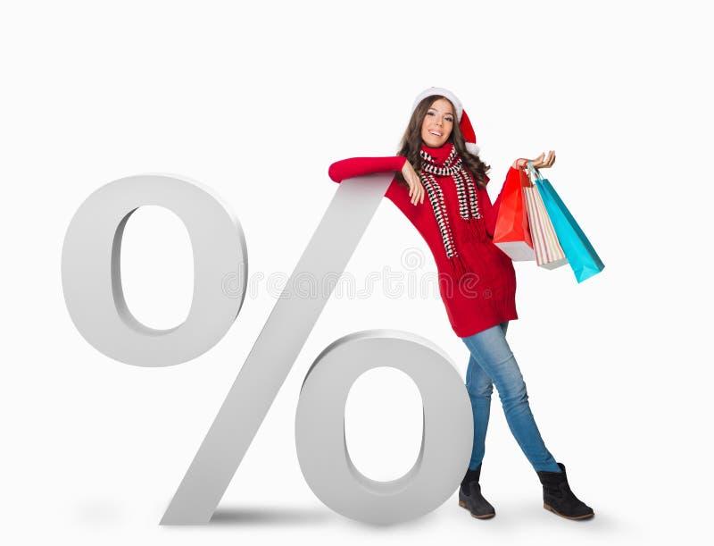 Frau, die nahe bei einem Prozentzeichen steht lizenzfreie stockfotografie
