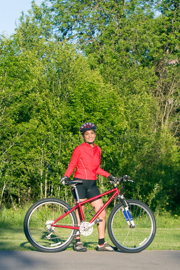 Frau, die nahe bei Fahrrad - Vertikale steht lizenzfreie stockfotografie
