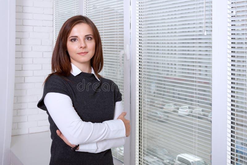 Frau, die nahe dem Fenster mit ihren Armen gekreuzt steht stockfoto